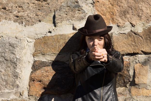 Женщина в шляпе делает пистолет руками и указывает на камеру