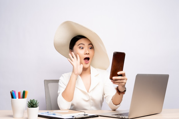 Woman wearing hat use smart phone taking a selfie at office isolated over background