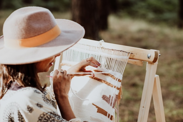 Woman wearing a hat and weaving a mat on a homemade loom in the backyard