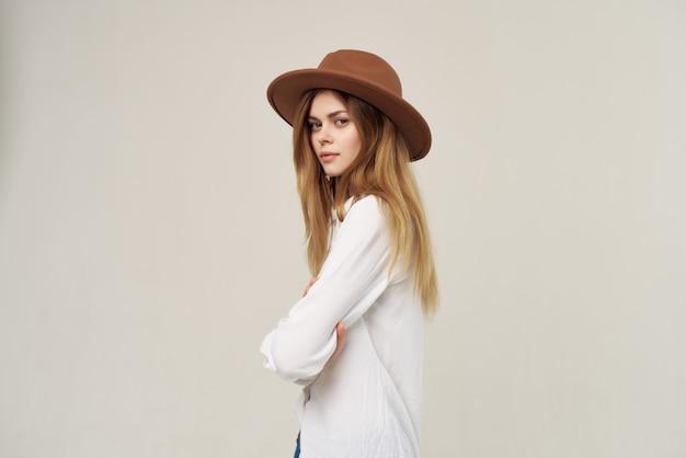 明るい背景のポーズをとって帽子白いシャツスタジオを着ている女性