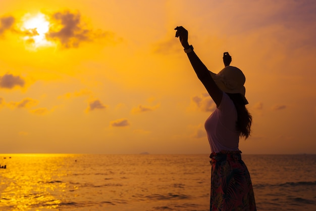 Woman wearing hat with arms raised standing on sea beach at sunset