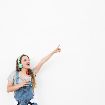 Woman wearing headphone holding glass of juice pointing finger against white backdrop