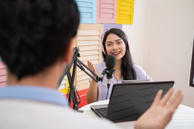 A woman wearing headphones during a podcast with a man