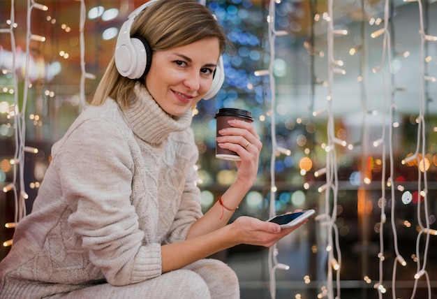 Woman wearing headphones holding cup and phone near christmas lights