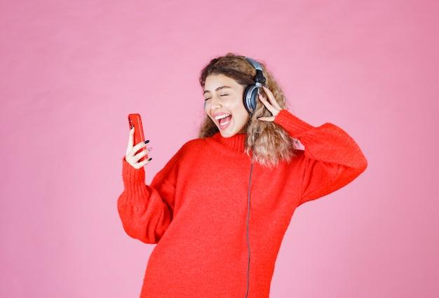 Donna che indossa le cuffie che ascolta la sua playlist sullo smartphone e balla.