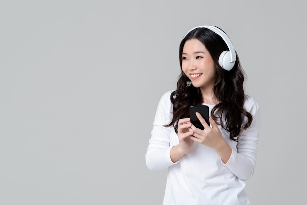 Woman wearing headphones listening to music from smartphone