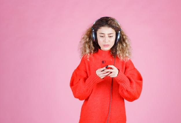 Женщина в наушниках слушает свой плейлист на смартфоне и выглядит недовольной.