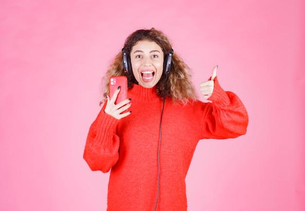 Женщина в наушниках, слушая ее плейлист на смартфоне и показывающая знак удовольствия.