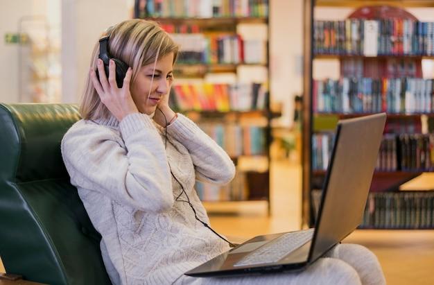 Наушники женщины нося смотря компьтер-книжку