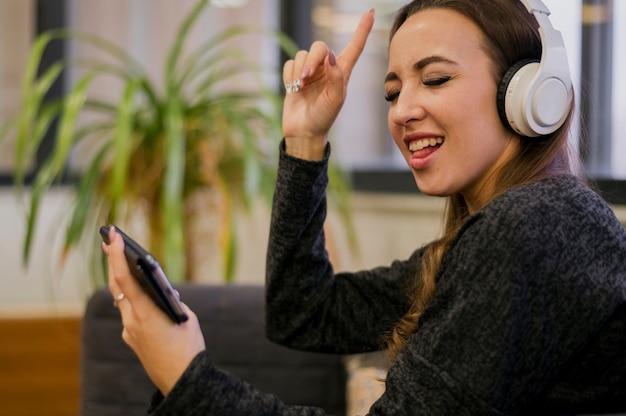 Наушники женщины нося смотря телефон и поя