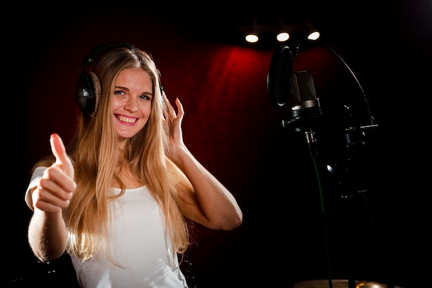 Woman wearing headphones showing thumbs up