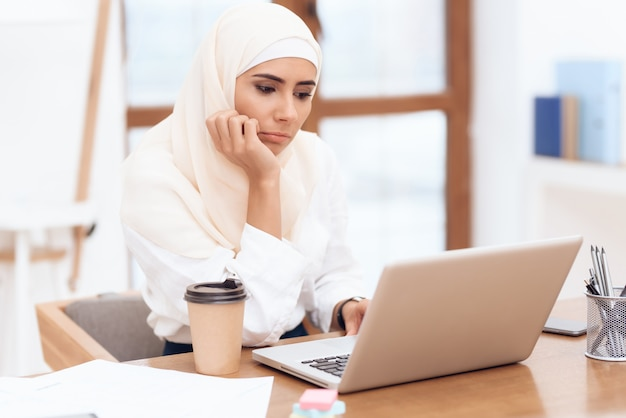 Woman wearing a headscarf sitting tired at work.