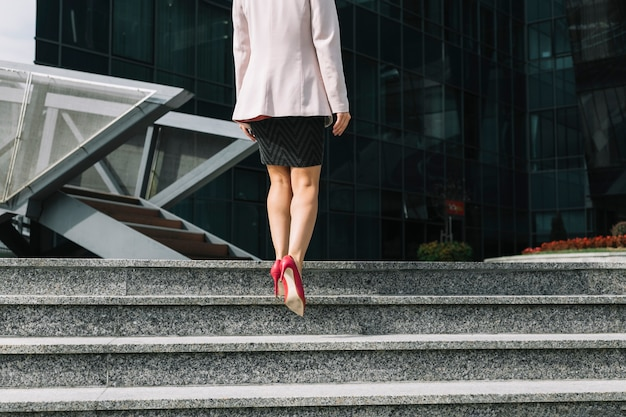 Woman wearing high heels walking on staircase