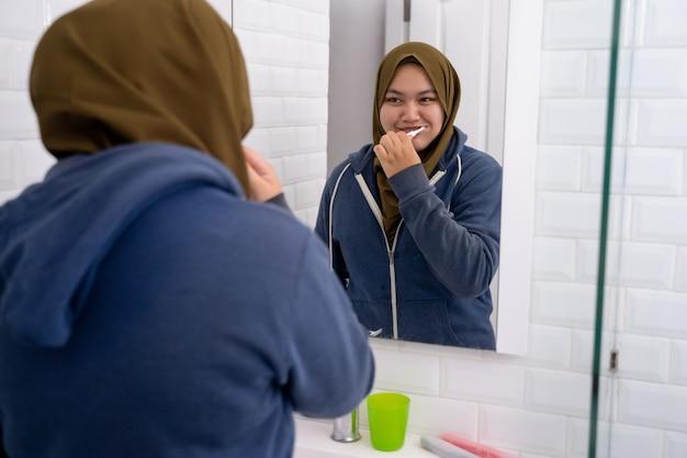 ヒジャーブを身に着けている女性は彼女の歯を磨く