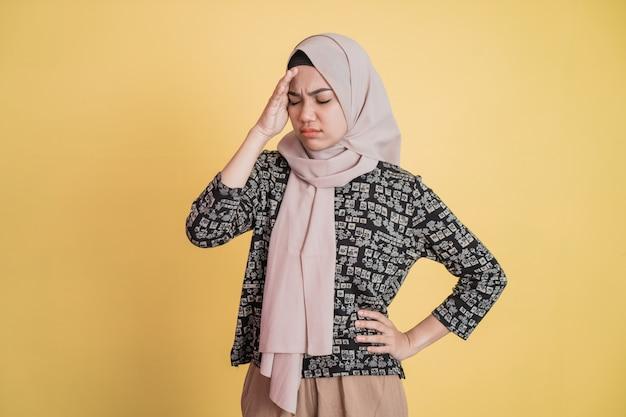 히잡을 쓴 여성은 머리를 잡고 서 있는 동안 한 손으로 허리를 잡고 어지럽고 스트레스를 받습니다.