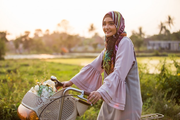 自転車に乗ってヒジャーブを着ている女性