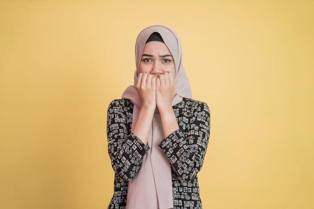히잡을 쓴 여성이 서 있는 동안 손가락을 물어뜯어 무서워한다