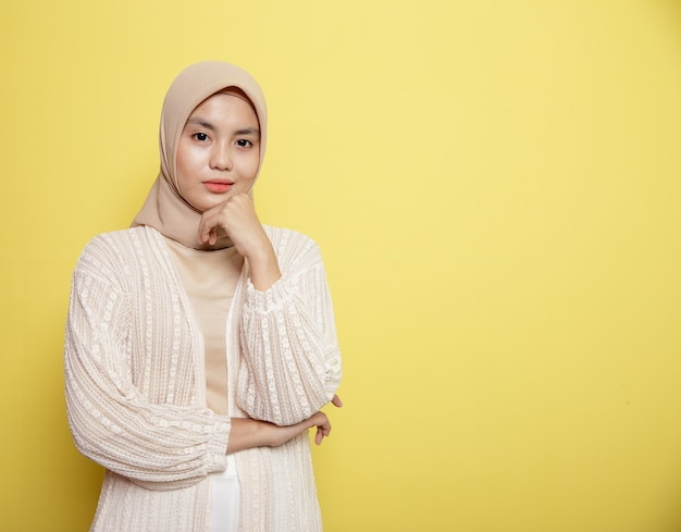 Женщина в хиджабе улыбается, держа челюсть, глядя в камеру, изолированную на желтом фоне