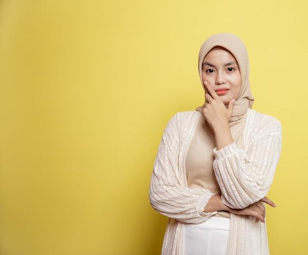 黄色の背景で隔離のカメラを見て彼女の顎を保持しているポーズをしながら笑顔のヒジャーブを着ている女性