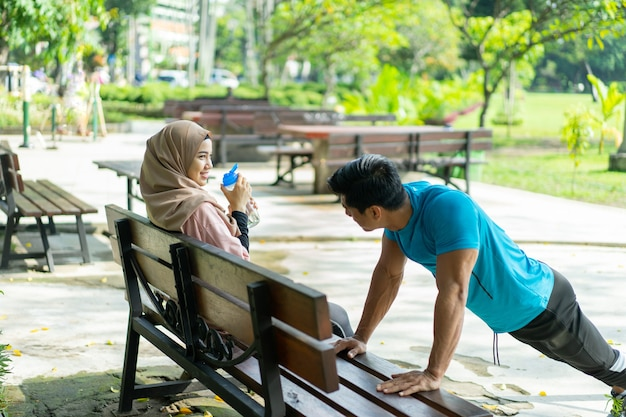 A woman wearing a hijab sportswear drinking with a drinking water bottle while sitting resting when with a male friend doing push up movements on a park bench
