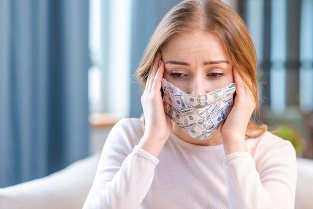 屋内で自家製のお金の顔のマスクを着ている女性