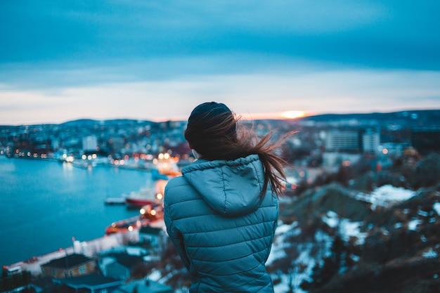 Женщина в пуховике с капюшоном смотрит на город днем
