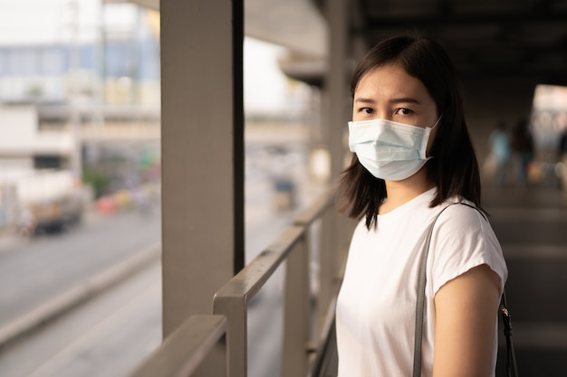 Woman wearing a hygiene protective mask to protect covid19 virus, covid-19 and pm2.5 while traveling in the crowded place. woman use face mask to protect coronavirus disease. 2019-ncov crisis.
