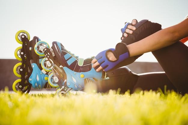 Woman wearing inline skates sitting in grass
