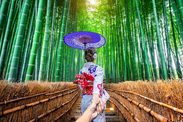 Woman wearing japanese traditional kimono holding man's hand and leading him to bamboo forest in kyoto, japan.