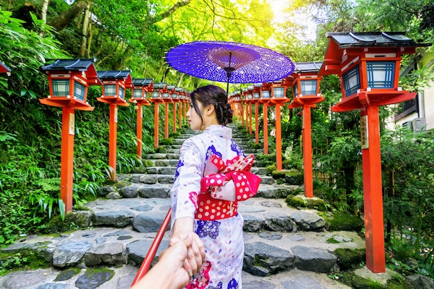 Woman wearing japanese traditional kimono holding man's hand and leading him to kifune shrine, kyoto in japan.