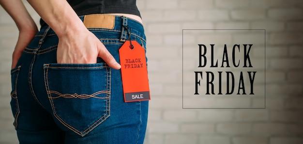ブラックフライデーのタグが付いたジーンズを着ている女性