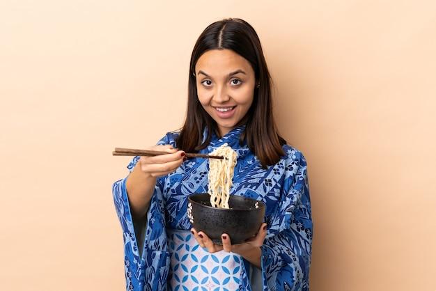 着物を着て、麺がいっぱい入ったお椀を箸で持って提供する女性