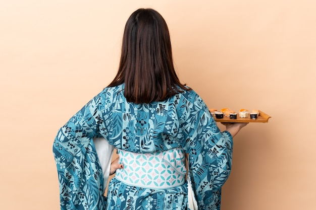 Женщина, носящая кимоно и держащая суши на изолированном фоне в заднем положении