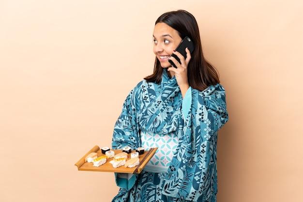 Женщина в кимоно и держит суши на изолированном фоне, разговаривая с кем-то по мобильному телефону