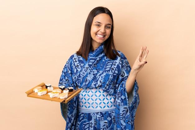 着物を着て、孤立した壁の上に寿司を持って幸せと指で3つを数える女性