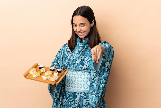 Женщина в кимоно и суши, держащая суши над изолированной стеной, делая жест по телефону и указывая вперед