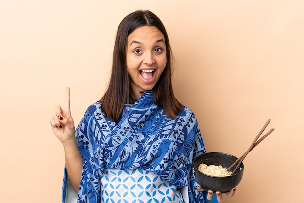 Woman wearing kimono and holding a bowl full of noodles pointing up a great idea while holding a bowl of noodles with chopsticks