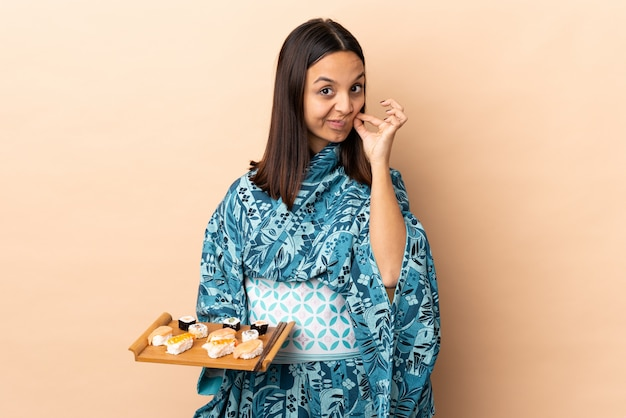 Woman wearing kimono and holding sushi over isolated wall showing a sign of silence gesture