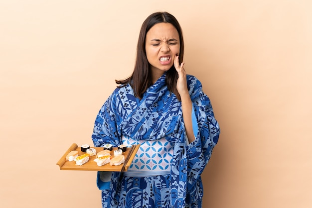 Woman wearing kimono and holding sushi over isolated wall with toothache