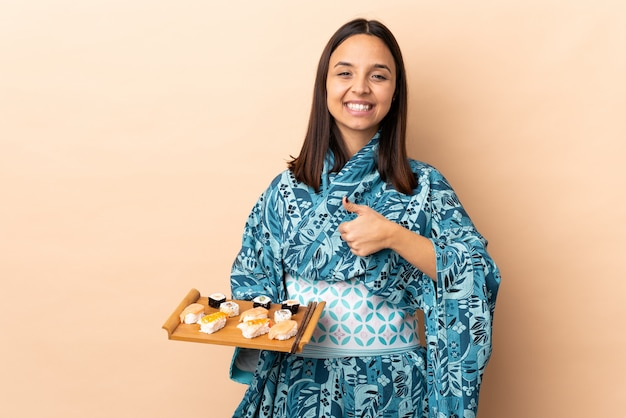 Woman wearing kimono and holding sushi over wall giving a thumbs up gesture