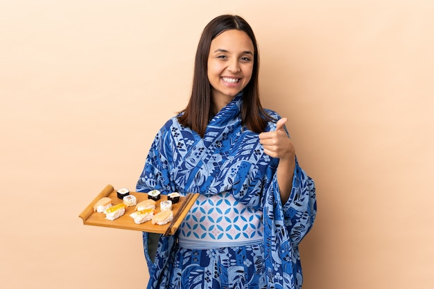 Woman wearing kimono and holding sushi over wall holding blank space imaginary on the palm to insert an ad and with thumbs up