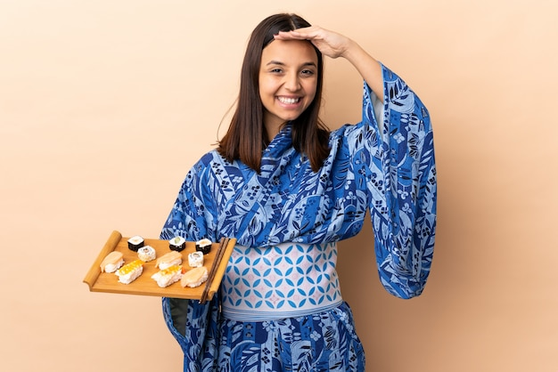 Woman wearing kimono and holding sushi over wall saluting with hand with happy expression
