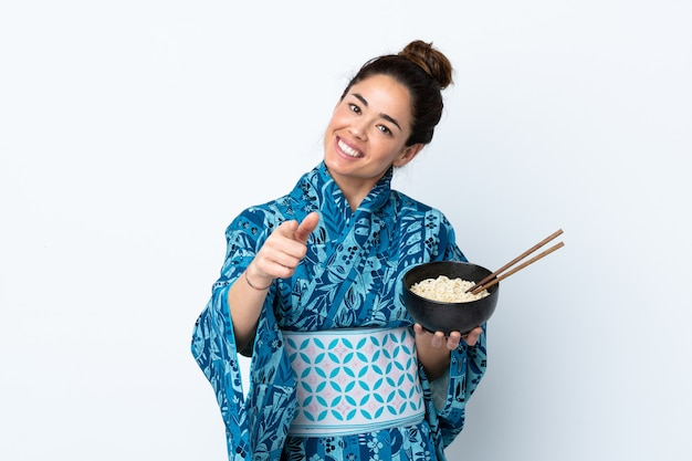 Woman wearing kimono over isolated white points finger at you with a confident expression