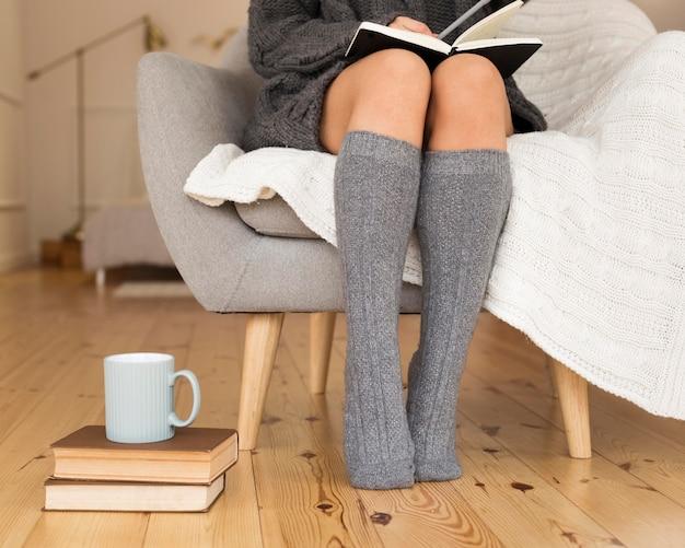 肘掛け椅子に座っているニーソックスを履いている女性