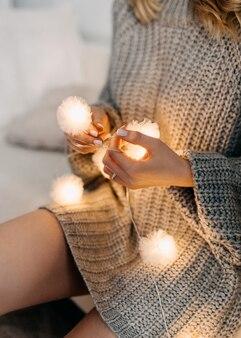 ライト付きガーランドを保持しているニットのセーターを着ている女性