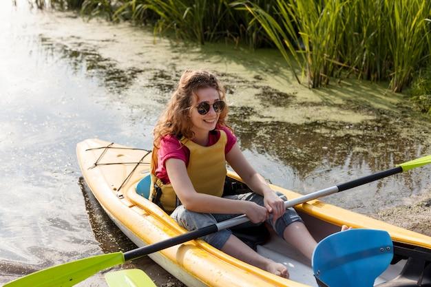Woman wearing life vest staying in kayak