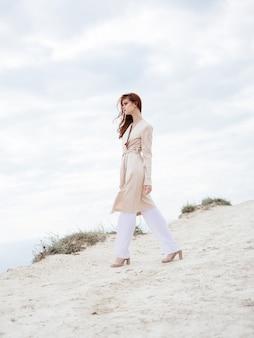 自然と砂のモデルの靴で完全に成長している軽い服を着ている女性