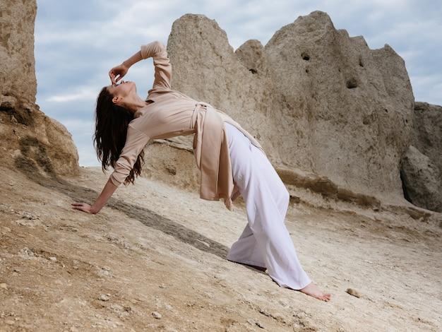 岩や高い石の近くの砂の上に軽い服を着ている女性