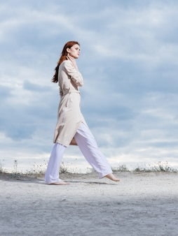 A woman wearing light clothes walks on the sand in nature and clouds in the background.