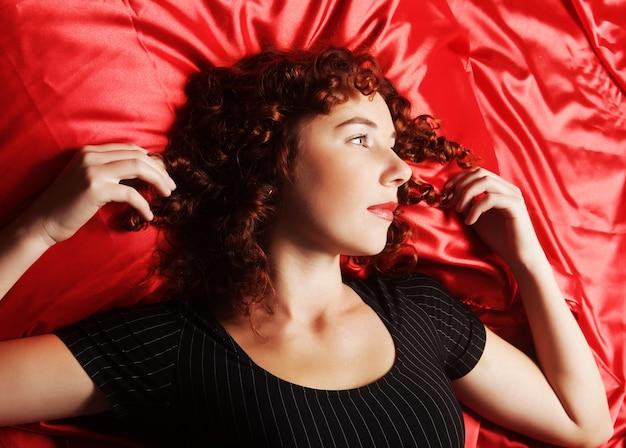 Женщина в нижнем белье, лежа на кровати